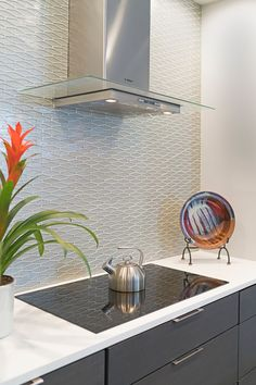 """Close-up view of this stunning backsplash in iridescent mosaic glass tile in """"Platinum"""". Countertops are Artic White Quartz."""