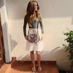 White denim button down skirt. Aztec print forest green top and an amazing purse. And cannot forget the gold and black sandals.