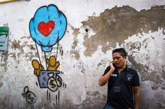 [photo by Francis Roux] A man chats on his mobile beside a cartoon graffitied on a weathered wall of people in a hot air balloon throwing money bags from the basket, Chinatown, Bangkok, Thailand