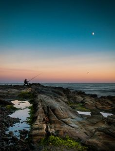 Night fishing under a full moon at Cranfield Beach. The haze of the evening sunset was setting from the Cooley Mountains - County Down, Northern Ireland - Via Jarlath Gray