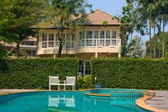 2-story contemporary home with pool in backyard bordered with tall sculpted hedge.