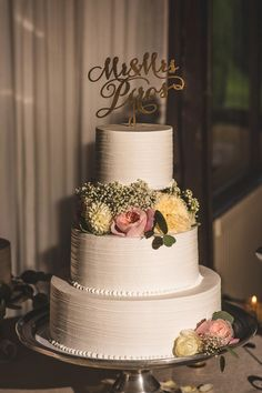 Elegant wedding cake idea - white three-tiered wedding cake with blush + ivory flowers and gold laser-cut topper {Nick + Danée}