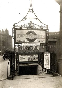 """The stairway at King's Cross in 1925. The sign above the stairs bears the name of the company that built and operated this tube line, the City and South London Railway. In 1890 this  privately-funded venture became the first deep-level underground """"tube"""" railway in the world and the first major railway to use electric traction."""