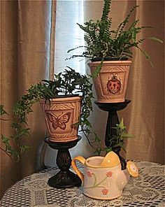 Place small potted plants in dollar store pots and sit them on wide candlesticks.