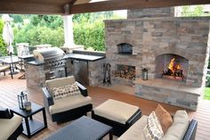 101 Outdoor Kitchen Ideas and Designs (Photos) : Hardwood flooring, black wicker furniture, and exposed ceiling beams fill out this outdoor kitchen space. A large fireplace stands within the stone enclosure holding countertops, grill, and brick oven. Outdoor Rooms, Outdoor Living, Outdoor Decor, Outdoor Patios, Rustic Outdoor, Outdoor Ideas, Brick Oven Outdoor, Outdoor Bars, Pizza Oven Outdoor