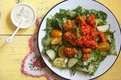 Buffalo Tempeh Ranch Salad 8 oz tempeh 1 tablespoon olive oil 4 cloves garlic, minced 1/2 cup vegetable broth 1/2 cup Frank's Red Hot hot sauce 2 teaspoons dried oregano 1/4 cup vegan mayo 1/4 cup unsweetened unflavored almond or soy milk 2 tablespoons fresh lemon juice 1/2 teaspoon garlic powder 1 teaspoon onion powder 1 teaspoon nutritional yeast 3 tablespoons fresh chives 2 romaine hearts 1/2 cup cherry tomatoes 1/2 cup cucumbers