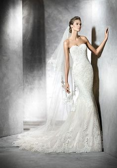 Princia by PRONOVIAS. Mermaid-style beige tulle wedding dress with lace appliqués and guipure. l TheKnot.com