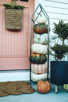 New fall front porch with newly painted pink door | Nesting with Grace | This year, we had fun with a fresh coat of salmon colored paint, loads of pastel pumpkins, and creative winter flower pots. #fallporch #pumpkins
