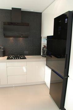 Biało czarna kuchnia, czarna cegła w kuchni, białe meble, czarna lodówk.a Zobacz więcej na: https://www.homify.pl/katalogi-inspiracji/28511/kuchnia-w-czerni-i-bieli-6-przykladow