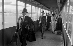 Old photo of an airport in 1956. People dressed up for traveling by plane. Airline travel was a privilege and people dressed up for the occasion.