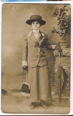 Real photo postcard of young woman with umbrella, straw hat and fringed handbag - circa 1910.
