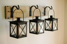 Black Lantern Trio hanging from wrought iron hooks on recycled wood board for unique wall decor, home decor, bedroom decor on Etsy, $56.00