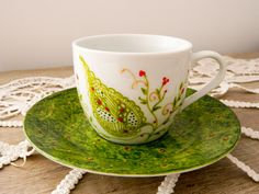 Hand painted tea cup with green leaf.