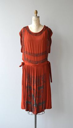 Antique 1920s brick red silk dress with elaborate cut steel beading forming a pair of elks on either side of a tree under stars, tunic style bodice with classic drop waist and side snaps.  --- M E A S U R E M E N T S ---  fits like: small/medium bust: best fit 36-38 waist: best fit up to 32 hip: free length: 41 brand/maker: n/a condition: very good, few very minor discolorations, some larger marks on skirt (see photo), 2 pinholes on bust  to ensure a good fit, please read the s...