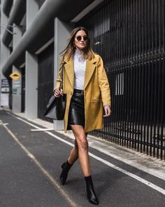 Como usar amarelo em diversos looks: guia completo. Blusa branca de gola alta, balzer oversized, calça de couro preta, ankle boot preta