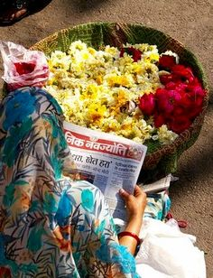 Flower Vendor catches up on the news while waiting for customers.