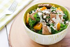 This hearty winter salad is made with massaged kale, roasted butternut squash, lentils, and pita chips, then dressed with savory tahini sauce.