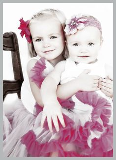 cute photo of sisters wearing pink flowers in their hair and pink tutus with white blonde hair and blue eyes