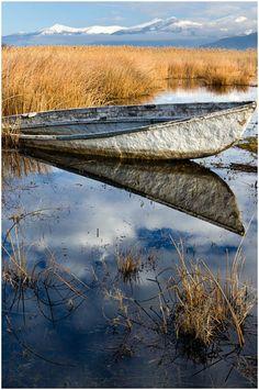 A white fishing boat lying abandoned at Prespa lake, Western Macedonia, Greece Macedonia Greece, Republic Of Macedonia, Outdoor Photos, Optical Illusions, Fishing Boats, Fresh Water, Abandoned, Reflection, National Parks