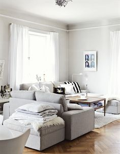 A white living room with grey sofa and various textiles