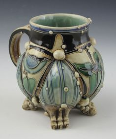 Carol Long Title: bird mug ]wheel thrown with cone 5 b-mix, pulled handle, hand built feet, slip trailing, commercial cone 5 food safe glazes, fired to cone 5 oxidation ]