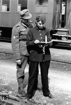 A German mountain trooper shows obvious appreciation to a female member of the Reichsbahn (Reich Railroad) service. Due to manpower shortages, women were extensively recruited into auxiliary and civilian agencies in an effort to free men for the front. Throughout the war, Hitler was particularly concerned that such engagement of female Germans could undermine the German family.