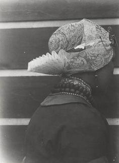 Jonge vrouw in Rooms-katholieke dracht van West-Friesland. Duidelijk zichtbaar is de katholieke manier van het omhoog spelden van de staart van de muts. ca 1910 #NoordHolland #WestFriesland