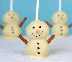 their core, they're your basic cake pops: cake crumbled and then mixed with frosting then rolled into balls and put onto lollipop sticks. I made vanilla cake and buttercream, then dipped them into melted white chocolate. Add some pretzels, edible ink and chocolate covered sunflower seeds and you've got an unmistakeable snowman – except they're tiny and delicious.