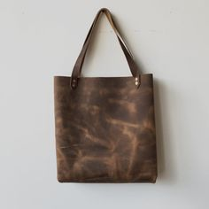 "-Every Day Tote in Rustic Brown.  - 15"" x 4"" 17""  -Hand set copper rivets.  -Cut & stitched from our hands to yours.  -Made from American cowhide from one of the oldest most distinguished US  Tanneries. a material that will last through life's adventures!  Since leather is a natural product the leather hides will be slightly  different from the photo shown as every item has unique markings.  Please allow 4-6 weeks for delivery. Since this is coming from my hands to  yours everything I make…"