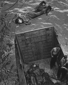 US Marines, wounded during the landings at Empress Augusta Bay, Bougainville, are lifted onto waiting hospital ship, 1943.