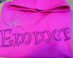 Emmer hoodie, written in the bubbly Curlz font with a pretty bling spray. Done in the purple rhinestuds and clear rhinestones to contrast against the hot pink hoodie.This kind of product can be fully personalised with different fonts/designs and colours of diamontes. For more info please visit our website or give us a call!