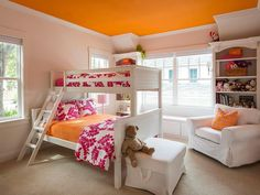 Adorable pink and orange shared girls' bedroom equipped windows flanking a white beadboard bunk bed dressed in orange and pink bedding accented with matching shams complimenting an orange painted ceiling.