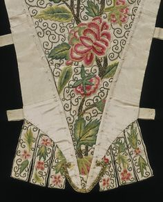 stomacher. English, 1730-1750.  Ribbed silk, hand-sewn and hand-embroidered with coloured silks and silver thread, printed cotton lining. VAM