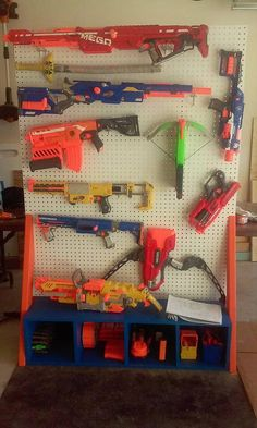 This is a fun way to display your kiddos NERF guns. and peg board are - Ideas of Nerf Gun - This is a fun way to display your kiddos NERF guns. and peg board are all you need. NERF gun rack is painted in NERF colors. Arma Nerf, Nerf Gun Storage, Nerf Toys, Nerf Games, Nerf Party, Toy Rooms, Baby Boy Rooms, Kids Room, Guns