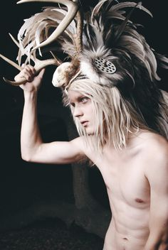 Blonde male model wearing a funky horned feathered head dress.