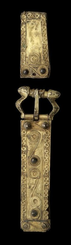 A Migration Period silver gilt buckle and strap end  Circa 5th-6th century A.D. Composed of sheets of silver, the front gilded and decorated with a border of spiralling filigree interspersed with knopped rivets, the buckle chip carved, 3½in (8.9cm) and 1¾in (4.4cm), mounted