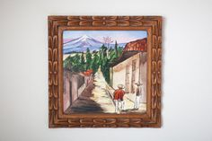 I love this hand painted tile because its in such a cool frame and has a lot of neat colors going on. The hand carved wooden frame is my favorite thing about this piece. Im unsure of when this was made, but I do know it is older. On the back it says Mexiko and there is a wire for hanging. All of our listings are second-hand, so please know that there may be some natural wear and tear.  8.5 in x 8.5 in    *Please DM me for International Shipping options