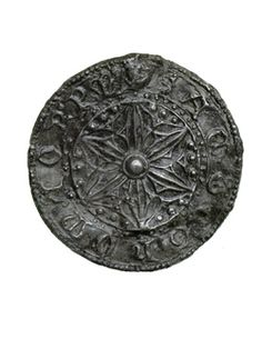 Pilgrim badge from the shrine of St Thomas Becket at Canterbury Cathedral. This badge is in the form of a disc decorated with a six-pointed flower (sexfoil) in the centre. Around the edge is an inscription: 'SANCT.THOMA OR PM' (meaning 'St Thomas pray for me'). This inscription was like a magical formula to protect the wearer of the badge. Production Date: Late Medieval; 14th century