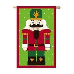 """This Nutcracker is a Christmas favorite! This Nutcracker flag is a perfect example of what Christmas truly is. It features a red border with a green background. The Nutcracker is placed directly in the center of the flag and is a traditional icon. An Applique flag is translucent individual pieces of fabric placed by hand and sewn together. It illuminates in the sunlight giving it a stained glass look. This flag is banner size and measures 28"""" x 44""""."""