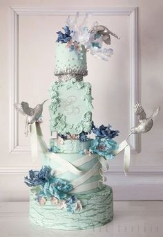 Simply magnificent wedding cake!  Mint acanthus leaves framing the couple's initials, wafer flowers, suspended silver hummingbirds...