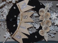 """Another holiday wreath. Take a wreath form, cover it with a sweater and add embellishments like the paper roses seen here and a """"wish"""" banner."""