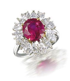 A ruby and diamond ring, by Harry Winston. The oval mixed-cut ruby, weighing 3.61 carats, within a surround of marquise and pear-shaped diamonds, mounted in platinum and 18k gold, diamonds approximately 1.75 carats total, signed Winston.