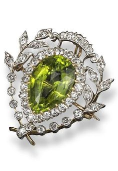 An early 20th century peridot and diamond brooch pendant by Pickslay & Co. The pear-shaped peridot is set within diamond-set laurels in platinum and gold. 2.7cm wide. #DiamondBrooches