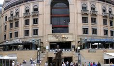 A sculpture of Nelson Mandela is a backdrop to a newscast in Nelson Mandela Square. The square anchors Sandton City, a popular upscale shopping center in Johannesburg, South Africa. Johannesburg City, Places Ive Been, Places To Go, Day Tours, South Africa, Street View, Explore, Nelson Mandela, Magazine