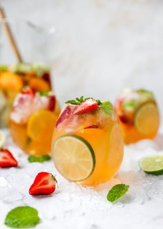 A glass of white wine sangria topped with extra strawberries and mint. Additional glasses are out of focus in the background.