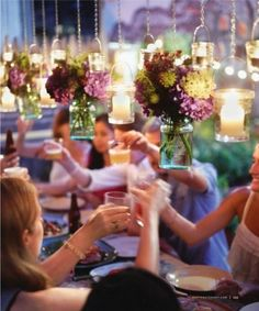 Hanging floral arrangements. Doesn't get in the way of guests talking across the table and draws more attention the flowers. Love it.