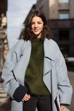 Olive green mohair jumper with a light grey oversized coat, black jeans and a white clutch bag | Image via bloglovin.com