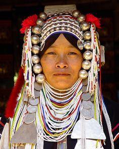 Portrait de femme Akha avec collier et coiffe ethnique traditionnelle.