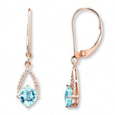 These elegant drop earrings for her each feature a cushion-cut blue topaz complemented by shimmering round diamonds, totaling 1/15 carat in weight. The earrings are styled in 10K rose gold and secure with Euro-wire backs. #SilverDropEarrings