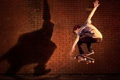 Back lighted by the warm light of setting sun, skater casts huge shadow on a massive red brick wall, when jumps along its length. Red Brick Walls, Walk On, Lifestyle Photography, It Cast, Warm, Sun, Sports, Hs Sports, Sport
